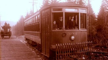 Photograph of the Hastings Streetcar taken at the terminus of the Hastings Streetcar line at Ellesmere Avenue in North Burnaby. Two men in uniform and a boy dressed in a suit and hat are at the head of the car, looking towards the camera. A horse-drawn cart full of cordwood is visible in the background moving along the planked wooden road parallel to the street car. (City of Burnaby Archives)