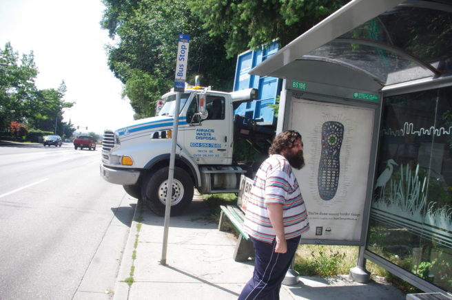 Truck blocking sidewalk and bus stop.